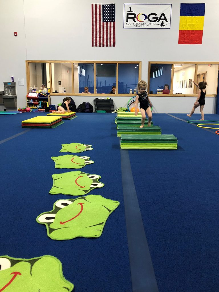 A child tumbling on green mats