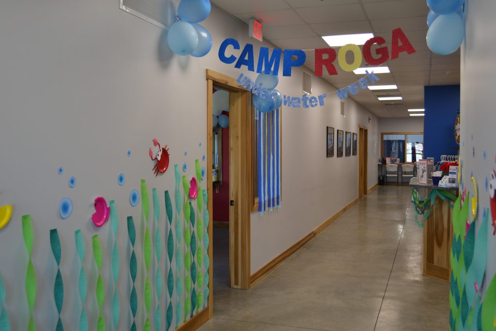 A hallway with Camp Roga signage