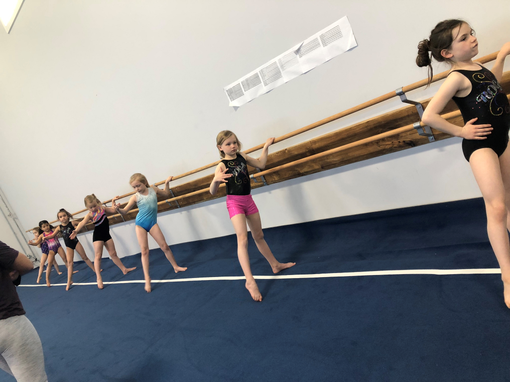 Girls team using barre